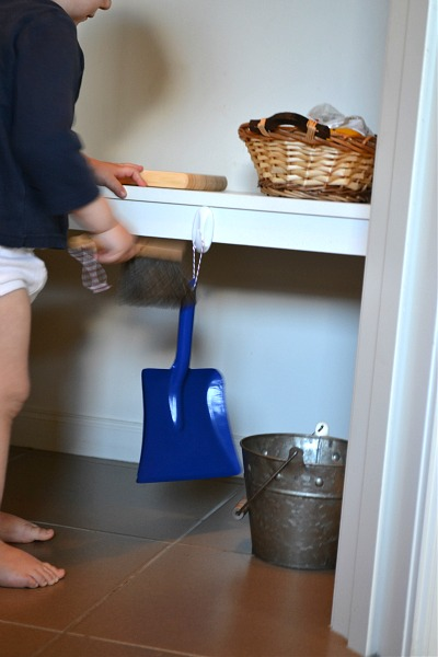 Otis standing in pantry with dustpan