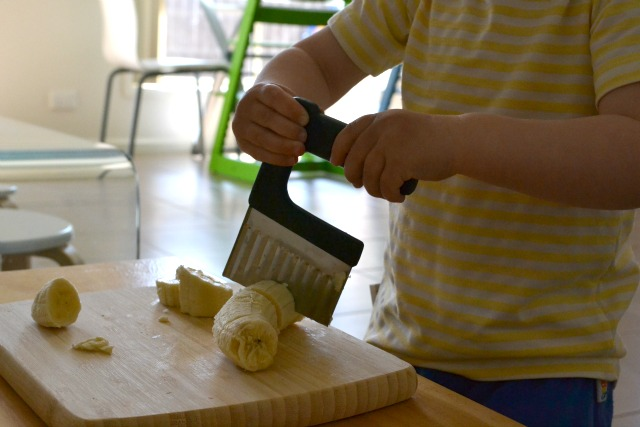 Slicing banana at 17 months