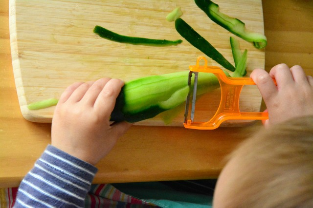 Toddler peeling cucumber