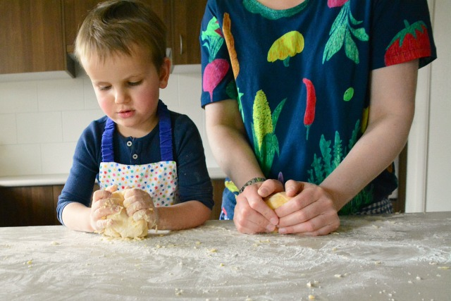 Kylie demonstrating to Otis how to knead using pasta dough for dinner