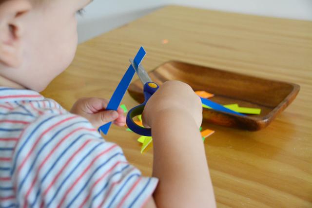 Cutting Otis toddler cutting at How we Montessori