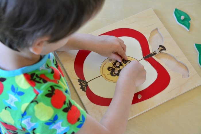 Otis with wooden apple puzzle at How we Montessori