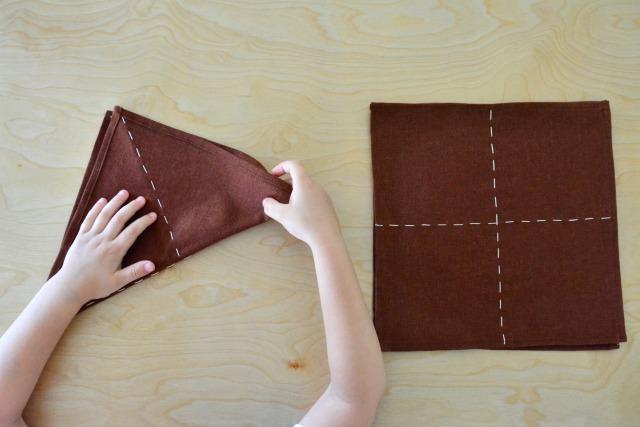 Otis neatly folding cloths at How we Montessori