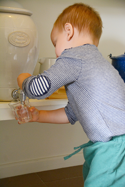Otis pouring a drink at drink station at How we Montessori