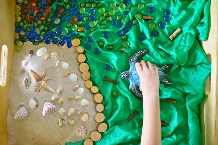 Otis with turtle, sand and playsilk in sensory tray at How we Montessori