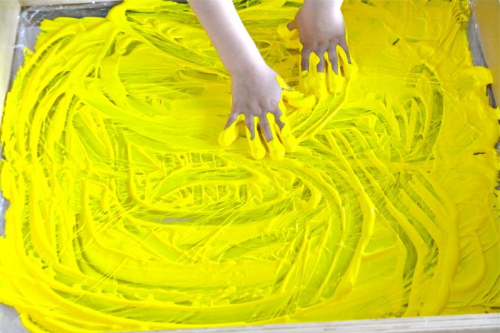 Otis with yellow paint in sensory tray at How we Montessori