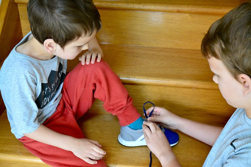 Caspar helping Otis with shoes, Multi age classrooms in Montessori and why siblings learn from each other
