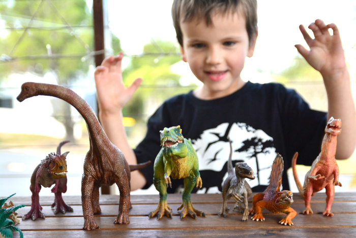 Otis playing with all of his Dinosaurs at How we Montessori
