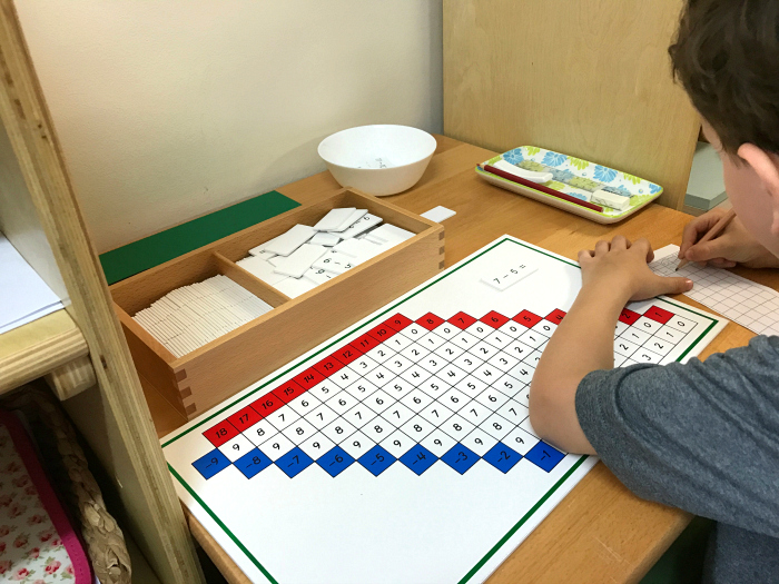 Otis doing some Montessori Math work at school - subtraction