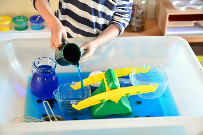 Otis playing with the water table at How we Montessori