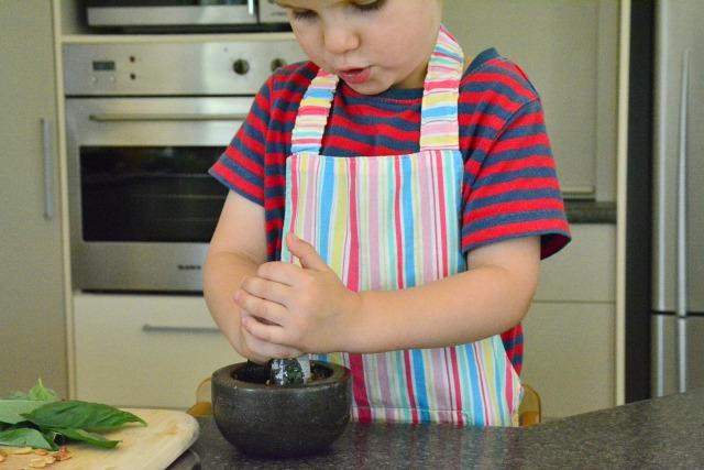 Otis making basil pesto