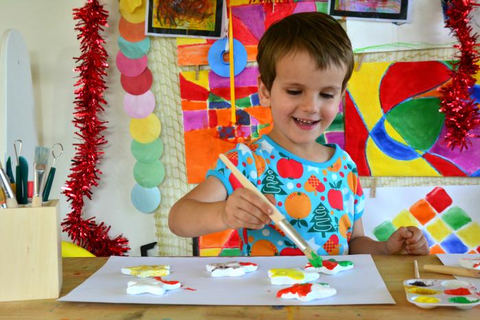 Otis painting salt dough ornaments for a handmade Christmas decorations at How we Montessori