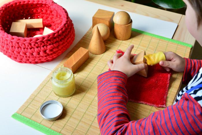 Otis polishing geometric soilds at How we Montessori, with beeswax polish