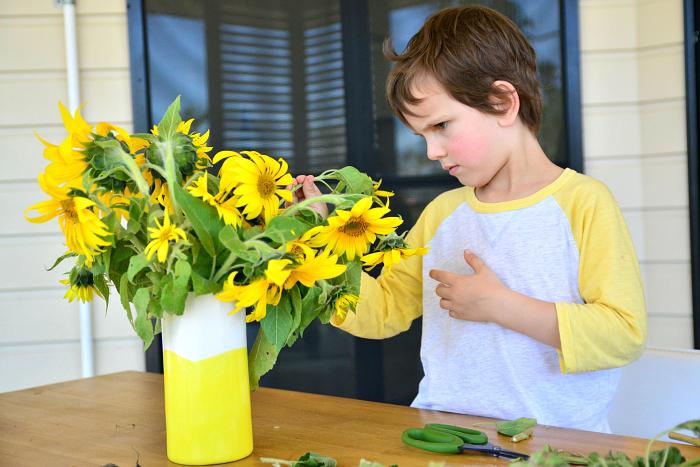 Otis cutting sun flowers from garden at HWM