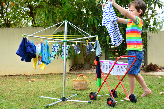 Otis using child size clothes line, clothes hanger at How we Montessori