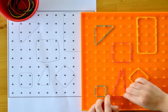 Otis making shapes on geoboard at How we Montessori