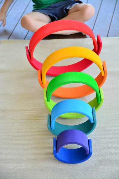 Otis making balancing circles with the Grimm's stacking rainbow