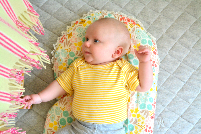 How we Montessori  Otto 9 weeks focusing on tassels on blanket