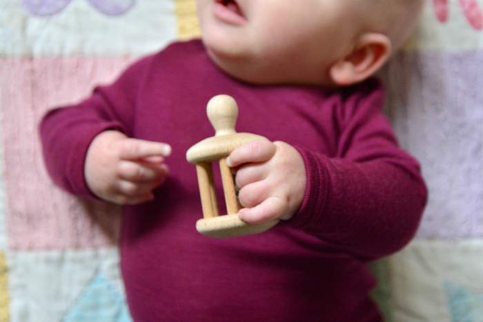 Otto reaching with hand  bell rattle at How we Montessori