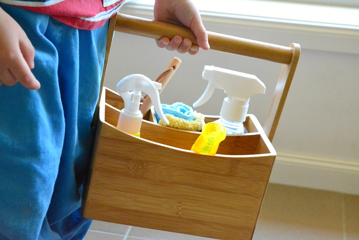 Otis holding his cleaning caddy @ How we Montessori