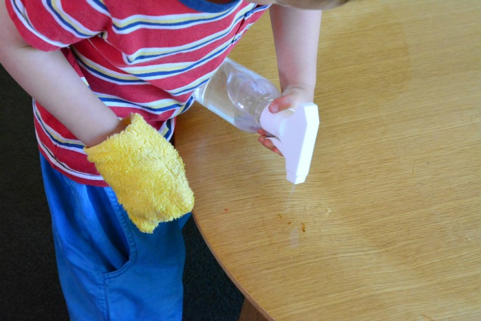 Otis wiping the table - using cleaning mitt and small spray