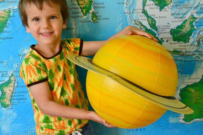 Otis holding Saturn at How we Montessori inflatable planets