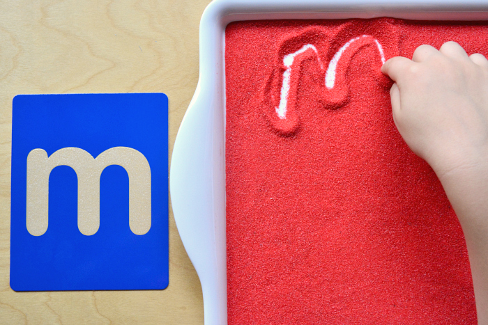 Sandpaper letter 'm' and sand tray at How we Montessori