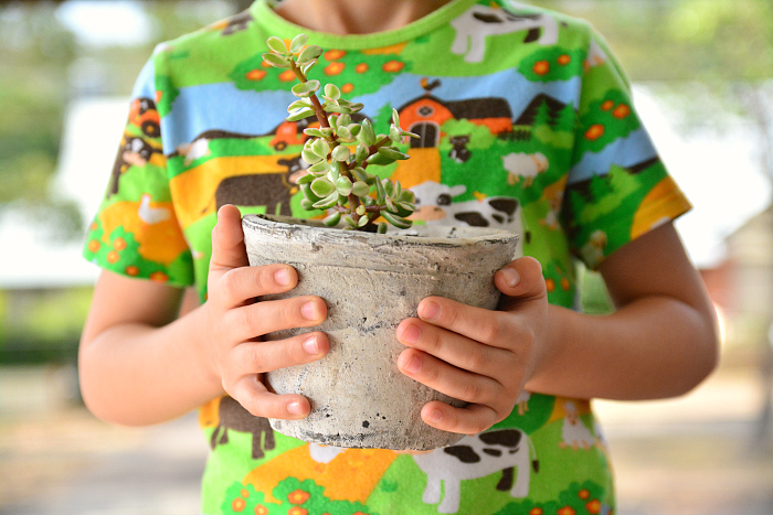Otis holding his little pot plant - Jade How we Montessori
