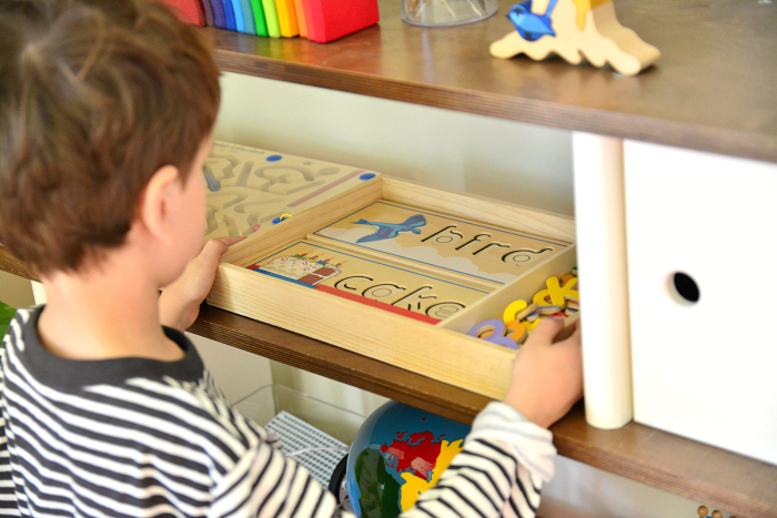 Otis with see and spell puzzle on shelf at How we Montessori