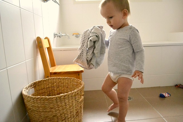 Otis toddler putting clothes in laundry basket at How we Montessori