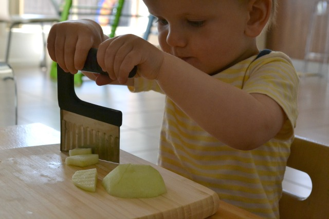 Otis cutting apple with crinkle cutter at 13-17 months