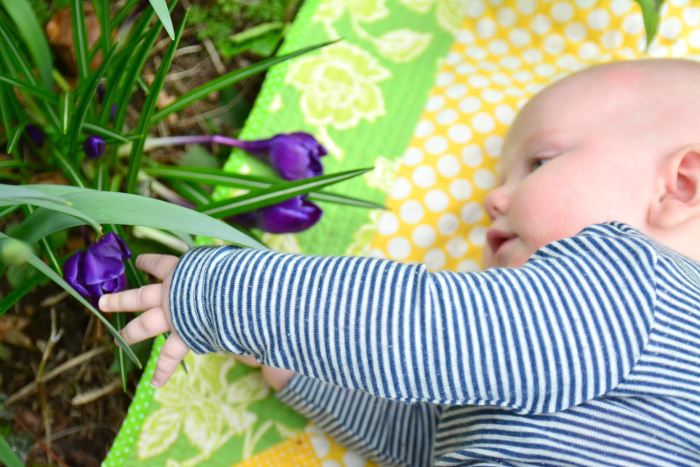 Otto grasping flowers in garden at How we Montessori at six months