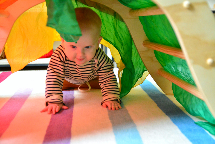 Otto crawling through the wooden arch  7 months at How we Montessori