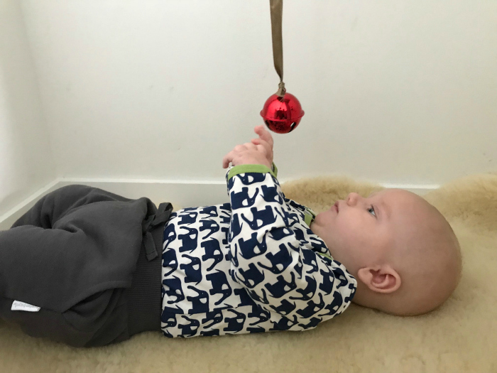 Otto using bell on a ribbon at a serviced apartment Brisbane at three months