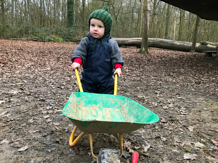 Otto using wheelbarrow at Forest School 16 months