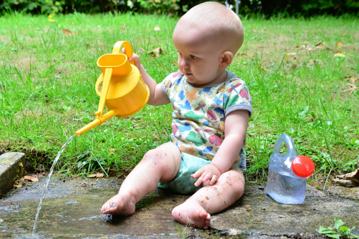 Otto watering garden at 11 months  practical life at How we Montessori