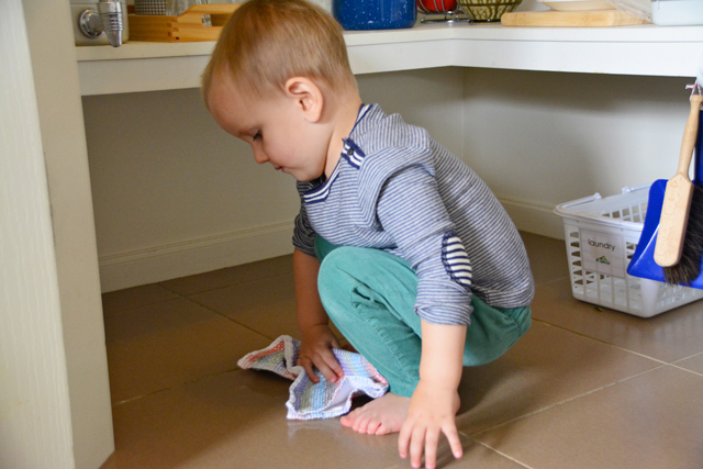 Otis toddler wiping up water spill at How we Montessori