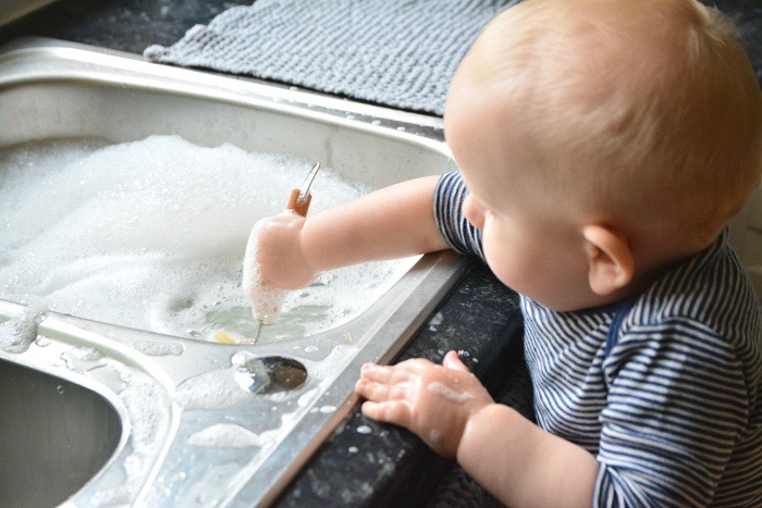 Otto washing dishes at 11 months at How we Montessori