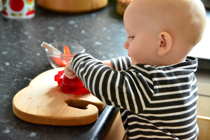 Ottos using strawberry slicer at 13 months