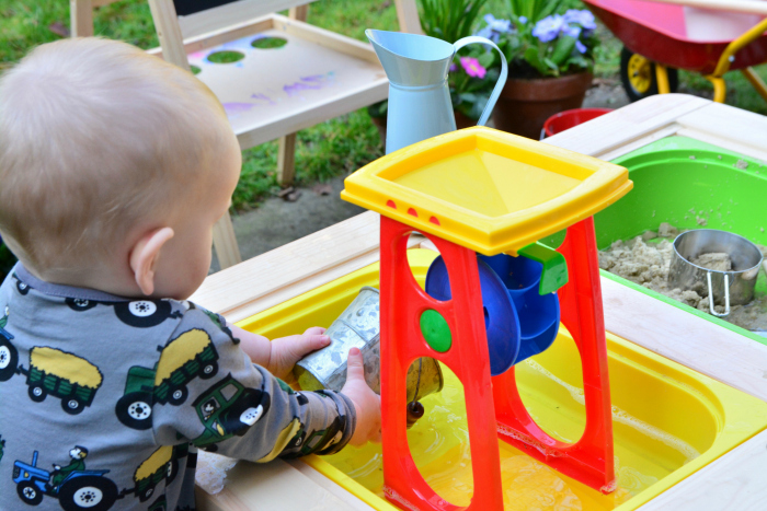 Outside water play at How we Montessori  17 months  water wheel and sand table