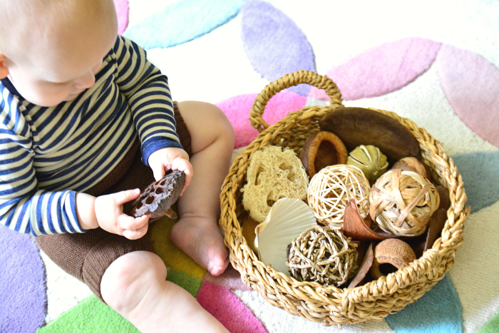 Otto at 10 months  with nature basket lotus pod at How we Montessori
