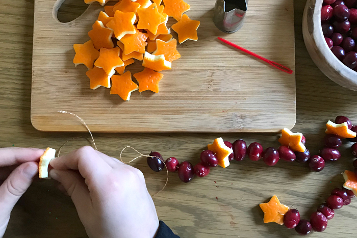 Otis threading making orange Christmas Pomanders at How we Montessori