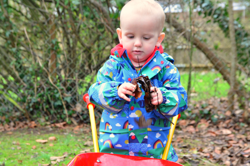 Otto with leaves in the garden in winter at How we Montessori