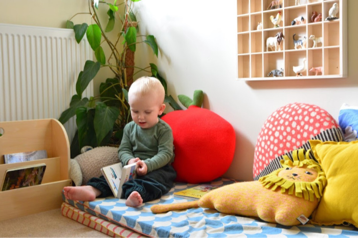 Montessori toddler bedroom Otto in reading corner at How we Montessori 17 months
