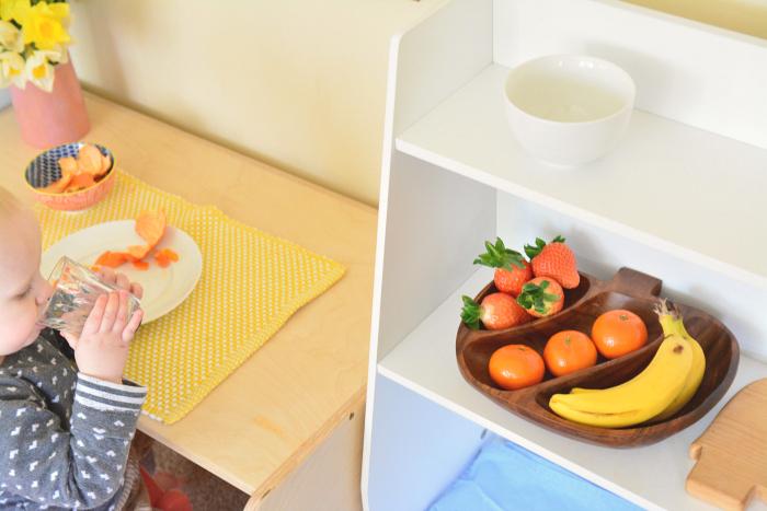 Montessori toddler peeling fruit at 17 months