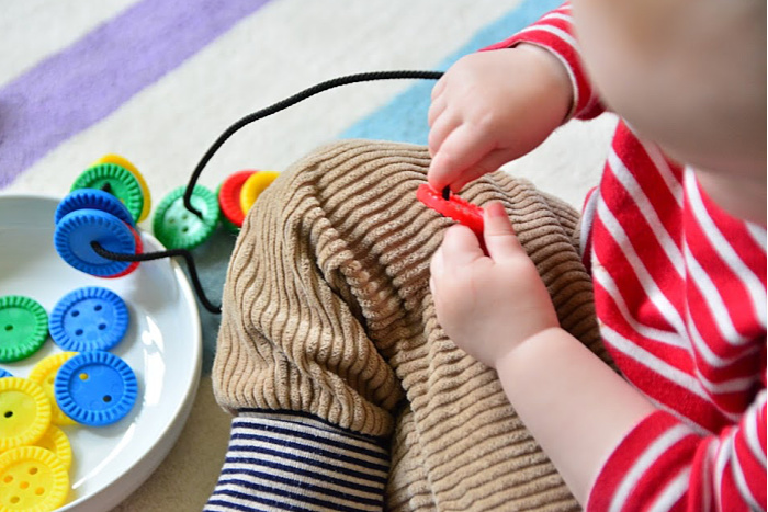 Otto threading oversize buttons at How we Montessori 17 months