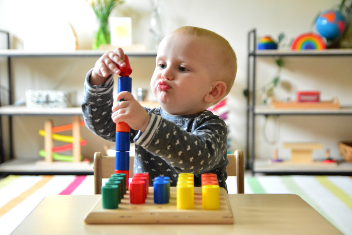 Otto 18 months at How we Montessori  concentration face  wooden stacking peg toy