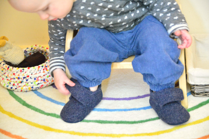 Otto putting on slippers at 18 months at How we Montessori UK
