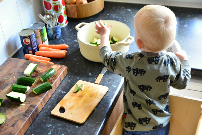 Montessori toddler chopping veg at How we Montessori 20 months
