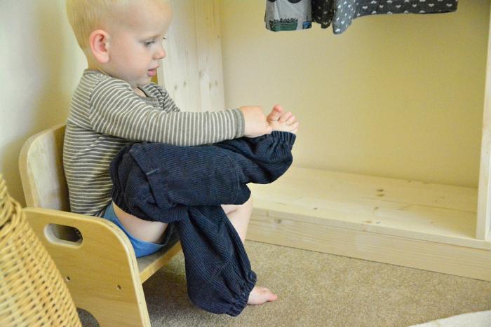 Otto reaching montessori wardrobe at how we montessori